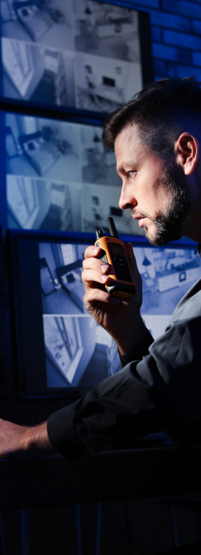 Male security guard with portable transmitter monitoring modern CCTV cameras indoors