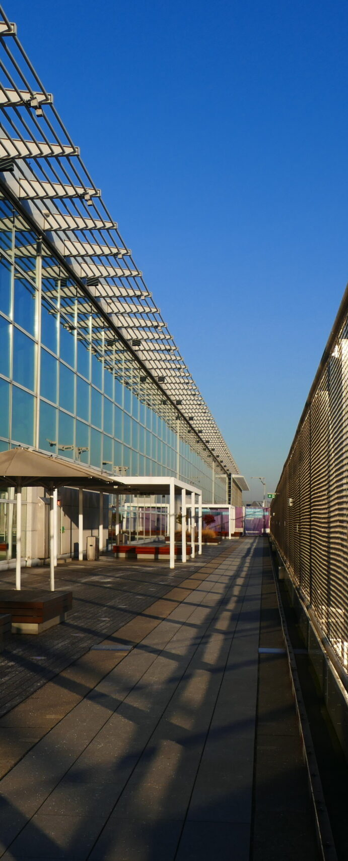 Terrace with modern architecture, security wire nets under blue sky and shadow structures on the floor.